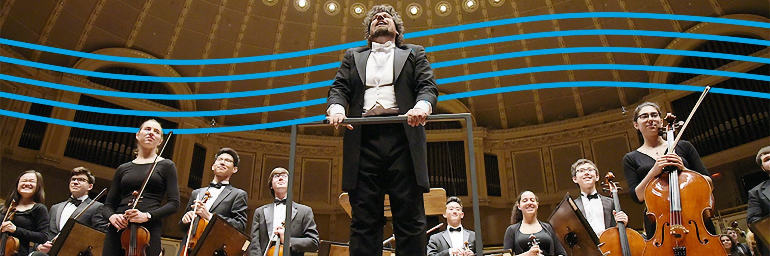 Photograph looking up at a stage with the conductor in the center surrounded by high-school-aged musicians standing with their instruments at the end of a performance