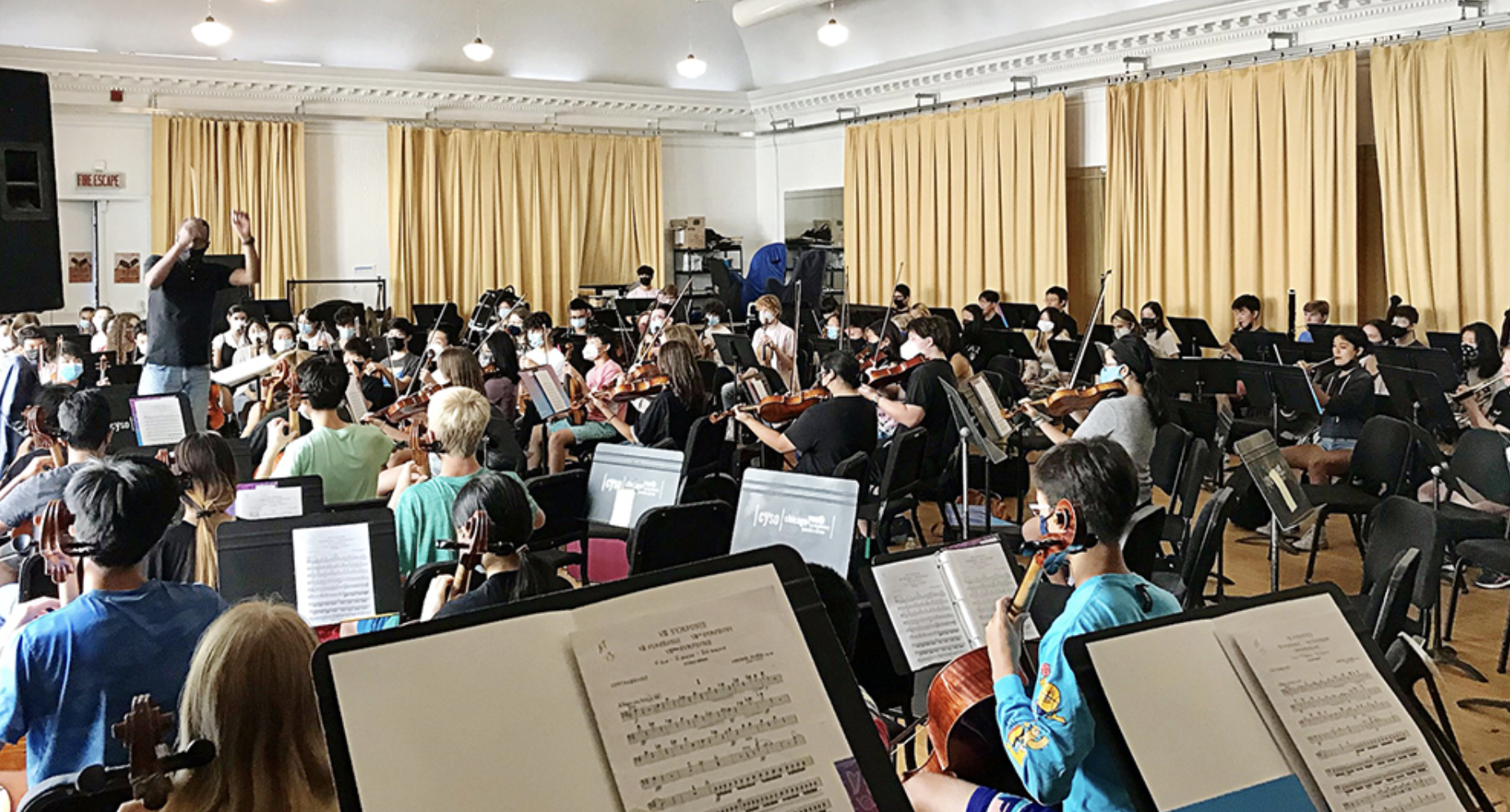 Philharmonic Orchestra rehearsal with conductor Terrance Malone Gray leading a packed room of young musicians