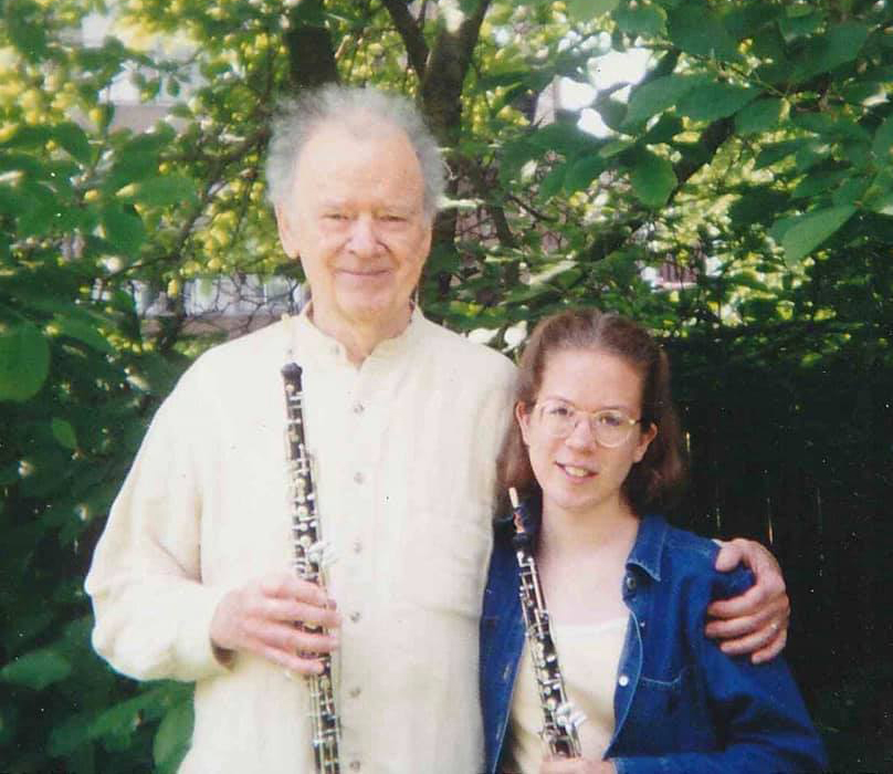 Photo of Ray Still holding oboe next to young Sonja Thoms also holding oboe in front of a tree background
