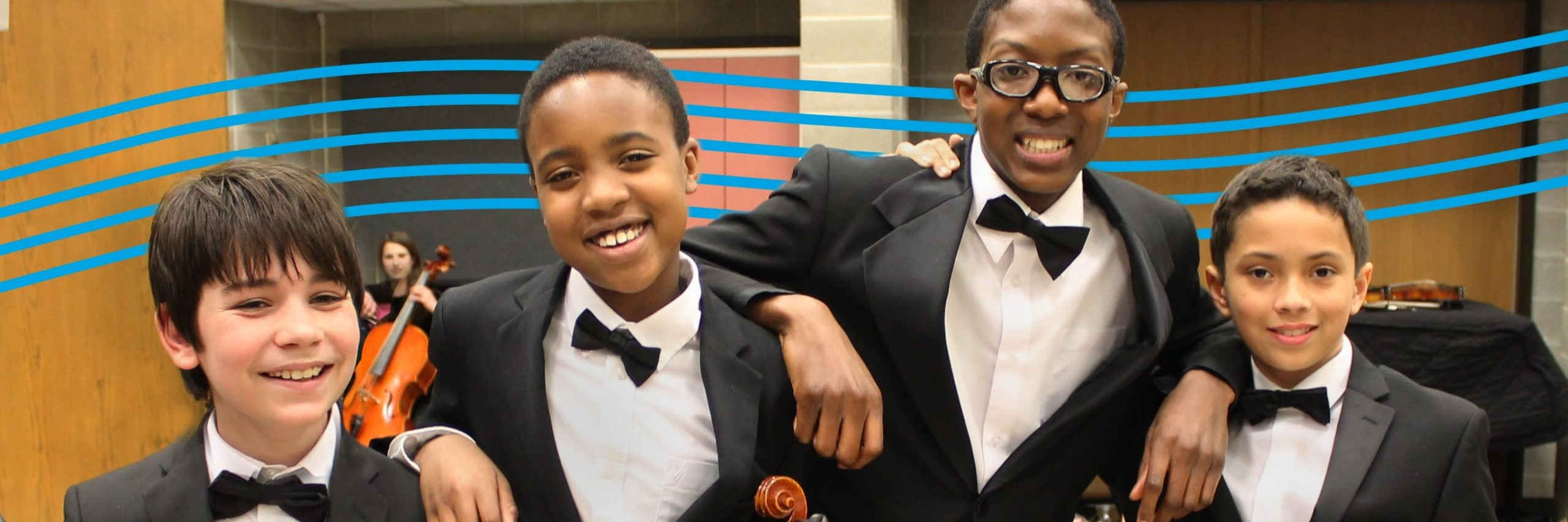 Four young male musicians in formal attire stand side-by-side and smile for a photograph